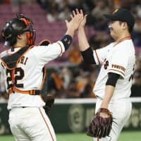 Giants pitcher Tomoyuki Sugano (left) and catcher Seiji Kobayashi celebrate after their win over the Dragons on Wednesday at Tokyo Dome. | KYODO