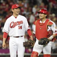 Carp starter Daichi Osera (left) and catcher Tsubasa Aizawa walk off the field after their win over the Dragons on Wednesday in Hiroshima. | KYODO