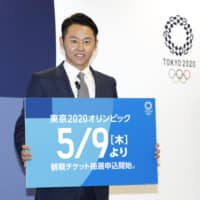 Four-time Olympic gold medalist Kosuke Kitajima displays information on how to apply for Olympic tickets at a media event in Tokyo on April 18. | KYODO