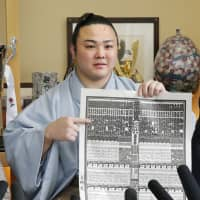 Enho points to his name in the latest banzuke, which was released on Tuesday ahead of next month's Summer Grand Sumo Tournament. | KYODO