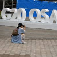 A woman takes a picture of a G20 Osaka design set up outside the venue for the G20 Osaka Summit Wednesday. | AFP-JIJI
