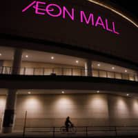 A woman rides past an Aeon shopping mall in Chiba in January 2018. | BLOOMBERG