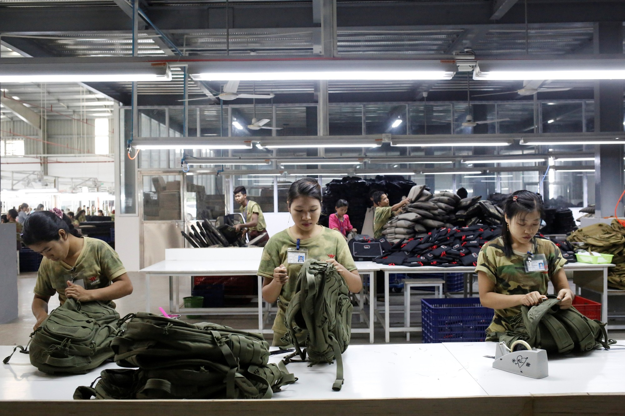 Workers conduct quality checks on products at a factory owned by Yakeda Outdoor Travel Products Co. in Yangon on June 11.   REUTERS