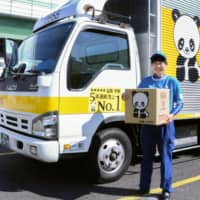 Asuka Maemura, a moving assistant at Osaka-based Sakai Moving Service Co., holds a package while working in Osaka earlier this month. | KYODO