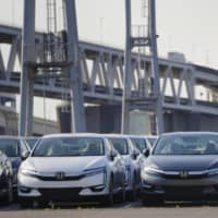 Cars ready to be exported are lined up at Yokohama port on May 23. | KYODO