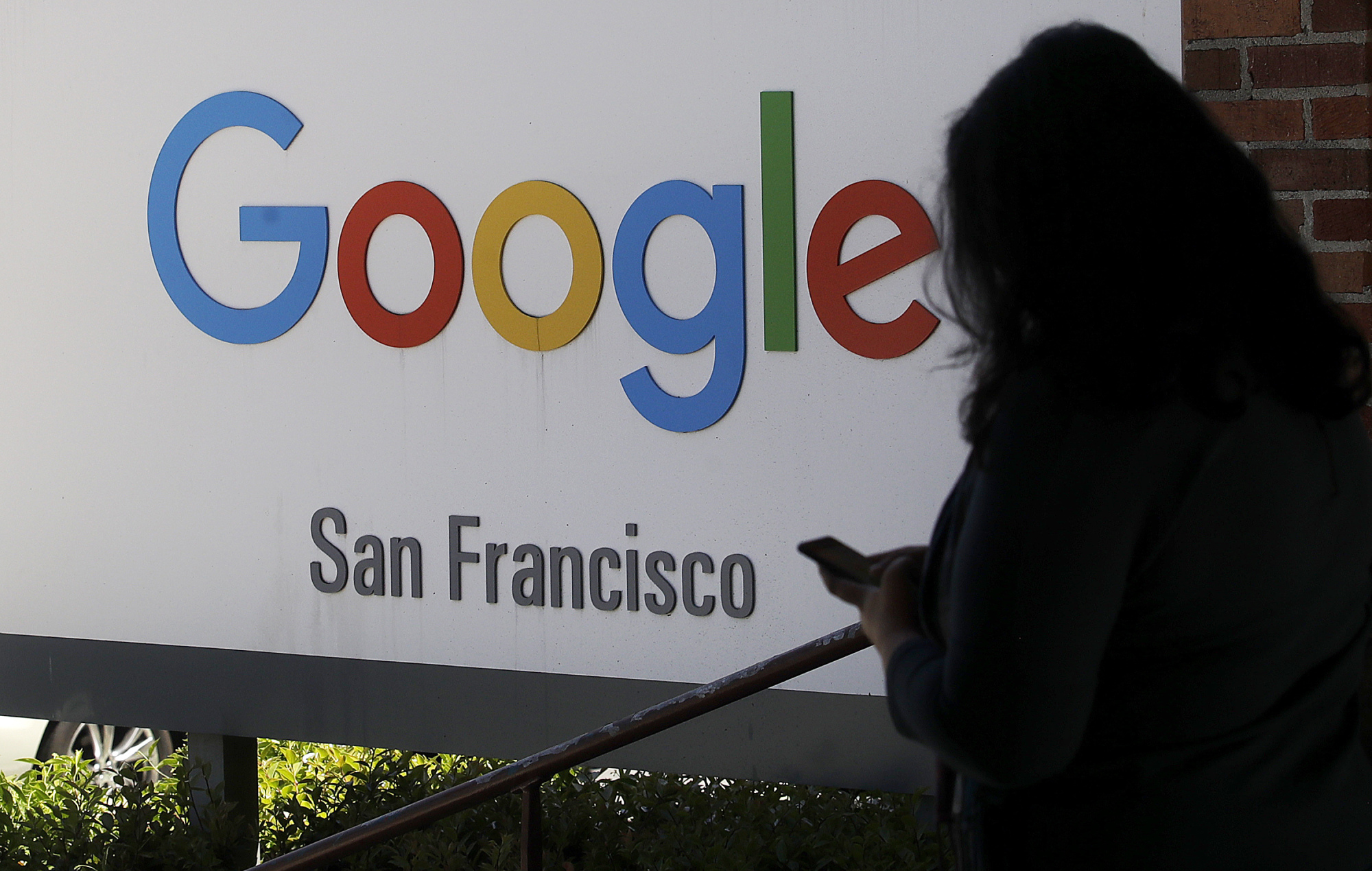 A woman walks past a Google sign in San Francisco in May. | AP