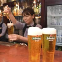 A bartender serves Heineken beer in Tokyo on Tuesday. Heineken Kirin K.K. expects demand for beer to surge during the Rugby World Cup due to the many fans who are due to visit from overseas to watch the tournament. | KYODO