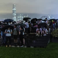 Protesters gather under umbrellas at Tamar Park outside the Legislative Council building in Hong Kong on Tuesday. Hong Kong braced for rare strikes and further protests amid an escalating standoff over a controversial bill that would allow extraditions to mainland China.   BLOOMBERG