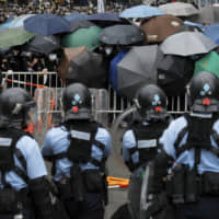 Policemen in anti-riot gear stand watch as demonstrators use umbrellas to shield themselves near the Legislative Council in Hong Kong on Wednesday. Hundreds surrounded government headquarters in protest of a highly controversial extradition law that would allow accused people to be sent to China for trial.   AP