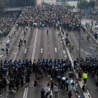 Protesters face off with police after they fired tear gas during a rally against a controversial extradition law proposal outside the government headquarters in Hong Kong on Wednesday.   AFP-JIJI