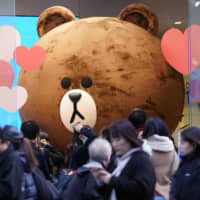 Pedestrians walk past the Line Corp. character known as Brown displayed at the Line Friends flagship store in the Harajuku district of Tokyo on Feb. 8. | BLOOMBERG