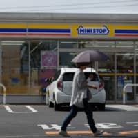 A pedestrian walks past a convenience store, operated by Ministop Co., in Sakura, Chiba Prefecture, in October 2016. | BLOOMBERG