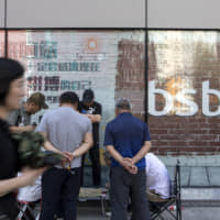 People play checkers outside a Baoshang Bank Co. branch in Beijing May 28. A Bloomberg index of Hong Kong-listed Chinese banks is set for its biggest monthly loss this year after regulators assumed control of Baoshang on Friday citing 'serious' credit risks. | BLOOMBERG
