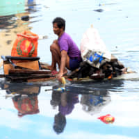 A man uses an improvised banca to collect plastic materials in a polluted river in Manila in 2016.   REUTERS