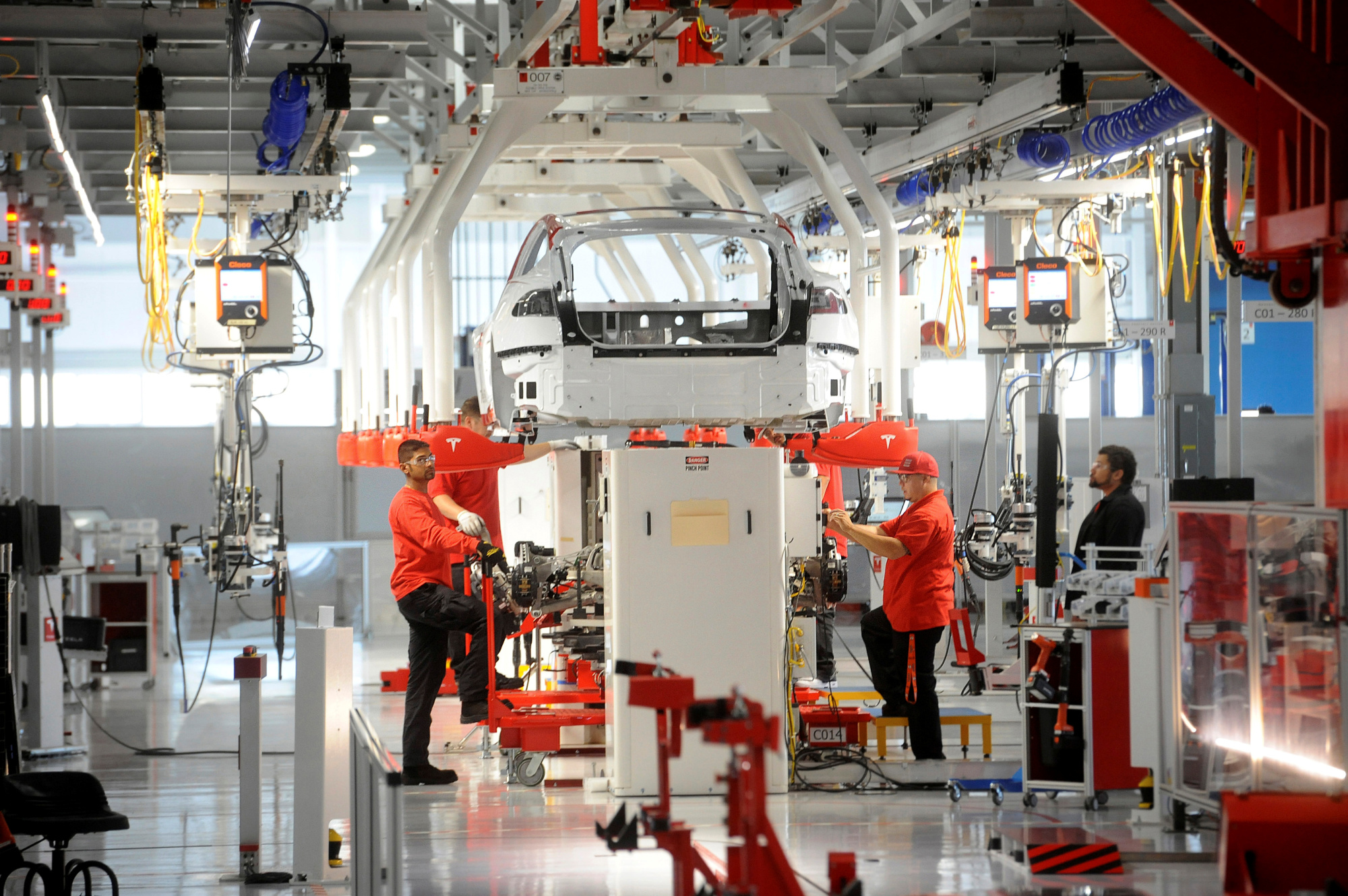 Tesla workers examine a Model S used for training and tool calibration at the company's factory in Fremont, California, in June 2012. | REUTERS