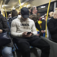 Passengers look at their smartphones as they ride a bus in Moscow on May 16. Russia's communications regulator says that Tinder is now required to provide user data to Russian intelligence agencies. | AP