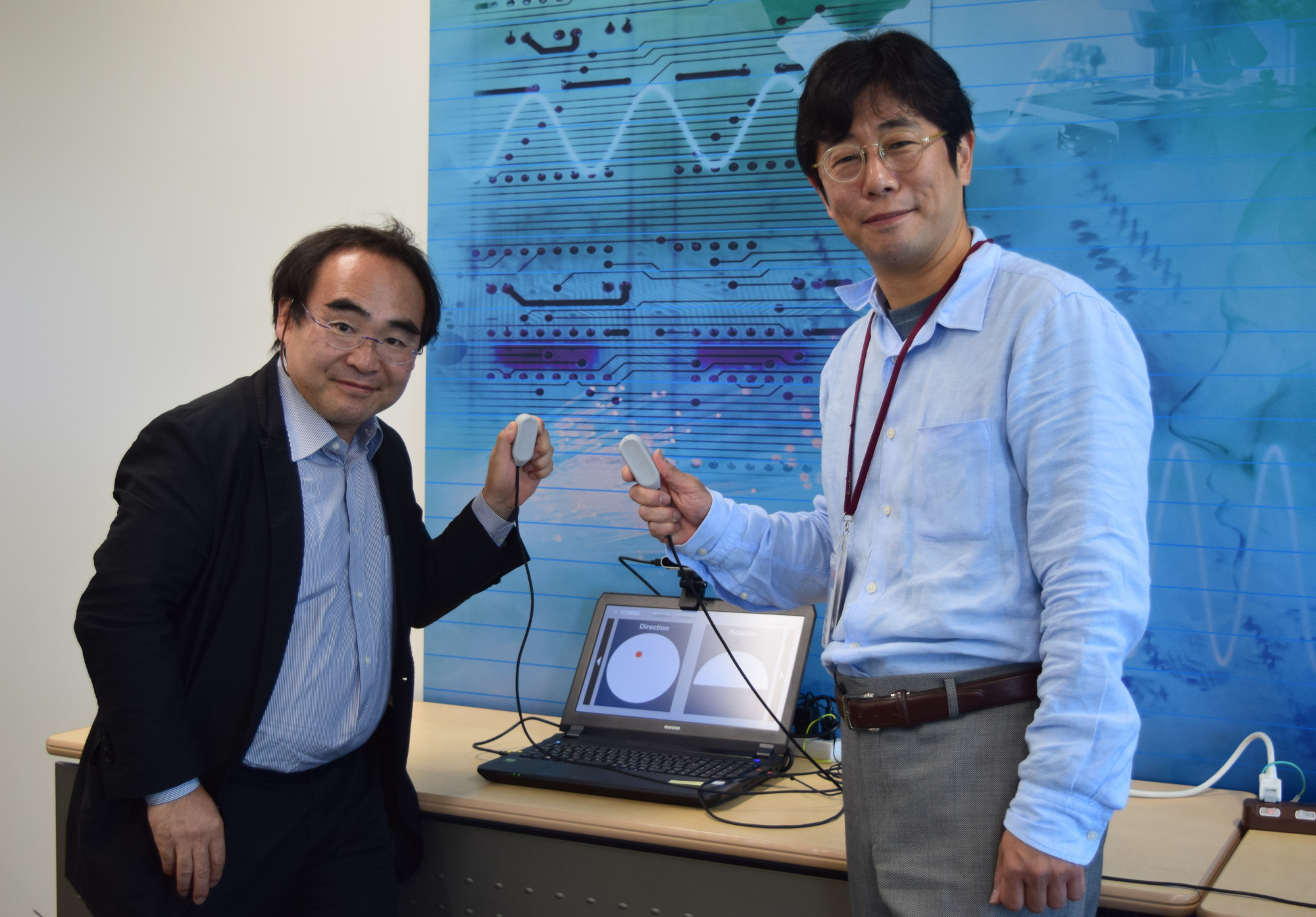 Miraisens Inc. CEO Natsuo Koda (right) and founder and Chief Technology Officer Norio Nakamura hold a palm-sized device equipped with 3D Haptics, which can recreate a variety of touch sensations in a three-dimensional space. | MASUMI KOIZUMI