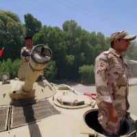 Iraqi soldiers sit on a tank at the entry of the Zubair oilfield after a rocket struck the site of residential and operations headquarters of several oil companies in the Burjesia area, in Basra, Iraq, Wednesday.   REUTERS