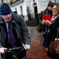 Then-London Mayor Boris Johnson cycles off after speaking to the media in front of his home in February 2016. | REUTERS