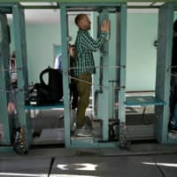 People pass through radiation measuring devices during a tour in the Chernobyl exclusion zone on June 7. HBO's hugely popular television series 'Chernobyl' has renewed interest around the world on Ukraine's 1986 nuclear disaster with authorities reporting a 30 percent increase in tourist demand to visit the affected area. | AFP-JIJI