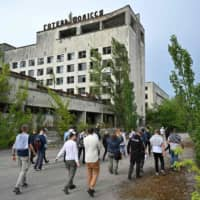 Visitors walk in the ghost city of Pripyat during a tour in the Chernobyl exclusion zone on June 7. | AFP-JIJI