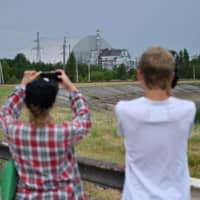 People take pictures of the Chernobyl nuclear plant and Chernobyl's New Safe Confinement covering reactor 4 during a tour in the Chernobyl exclusion zone on June 7. | AFP-JIJI