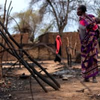 A woman looks at gutted houses during clashes between nomads and residents in Deleij village, located in Wadi Salih locality, Central Darfur, Sudan, Tuesday.   REUTERS