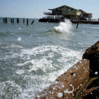 The rising waters of the Gulf of Mexico crash at the shoreline of the Treasure Island community of West Galveston Island, Texas, in 2014.   REUTERS