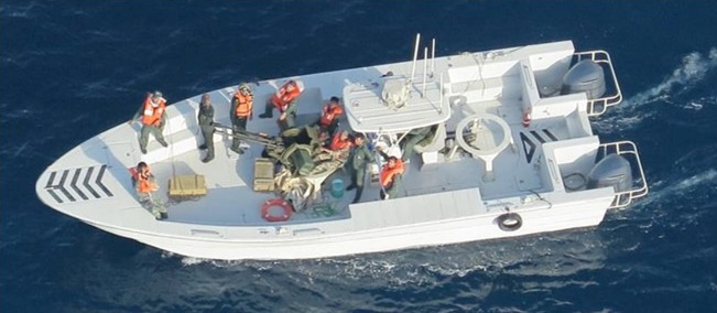 A U.S. military image released by the Pentagon in Washington on Monday shows what the Pentagon says are members of the Islamic Revolutionary Guard Corps Navy photographed from a U.S. Navy MH-60R helicopter after removing an unexploded limpet mine from the M/T Kokuka Courageous, a Japanese owned commercial tanker, after it was attacked with another mine that did explode on June 13. | U.S. NAVY / HANDOUT / VIA REUTERS
