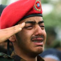 An unidentified son of deceased Maj. Gen. Gezayi Abera, who was killed by a bodyguard together with Ethiopian Army Chief of Staff Seare Mekonnen, salutes his father's flag-draped coffin during the funeral ceremony, in Mekele, Tigray Region, Ethiopia, Wednesday.   REUTERS