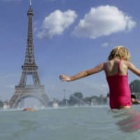 A girl cools off in the fountain of the Trocadero in Paris Tuesday. Authorities warned that temperatures could top 40 degrees Celsius (104 Fahrenheit) in some parts of Europe over the coming days, the effect of hot air moving northward from Africa. | AP