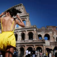 A tourist walks under the sun in front of the Colosseum in Rome on JTuesday during a heat wave. Meteorologists blamed a blast of torrid air from the Sahara for the unusually early summer heat wave, which could send thermometers up to 40 degrees Celsius (104 Fahrenheit) across large swaths of the continent. | AFP-JIJI