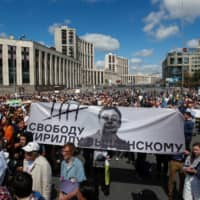 People attend a rally organized by Union of Journalists and approved by authorities in support of the investigative journalist Ivan Golunov in Moscow Sunday. The banner reads 'Freedom to Kirill Vyshinsky,' referring to the director of the Ukrainian office of the Russian state news agency RIA Novosti, who was detained on treason charges in Kiev in 2018.   REUTERS