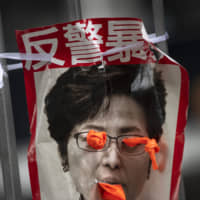 A defaced poster depicting Hong Kong Chief Executive Carrie Lam hangs at Tamar Park on Monday. | BLOOMBERG
