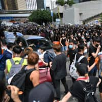Protesters occupy a main road outside the government headquarters in Hong Kong on Friday. | AFP-JIJI