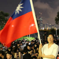 Protester Yung Xiu Kwan, 67, poses with a Taiwan flag during a demonstration against a proposed extradition bill, in Hong Kong on Monday. | REUTERS