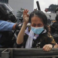 A protester is confronted by riot police during a massive demonstration outside the Legislative Council in Hong Kong on Wednesday. | AP