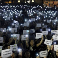 Hundreds of mothers holding placards, some of which read 'If we lose the young generation, what's left of Hong Kong,' and lit smartphones protest against the amendments to the extradition law in Hong Kong on Friday night. | AP