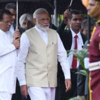Indian Prime Minister Narendra Modi and Sri Lankan President Maithripala Sirisena walk under an umbrella as they attend a welcoming ceremony for Modi at the Presidential Secretariat in Colombo on Sunday. | AFP-JIJI