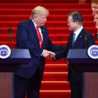 U.S. President Donald Trump shakes hands with South Korean leader Moon Jae-in during a joint news conference at the presidential Blue House in Seoul on Sunday. | AFP-JIJI