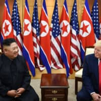 North Korean leader Kim Jong Un and U.S. President Donald Trump attend a meeting on the south side of the Military Demarcation Line that divides North and South Korea, in the Joint Security Area of Panmunjom in the Demilitarized Zone on Sunday. | AFP-JIJI