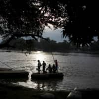 Migrants cross the Suchiate River on a raft from Tecun Uman, in Guatemala, to Ciudad Hidalgo, as seen from Ciudad Hidalgo, Mexico, Thursday.   REUTERS
