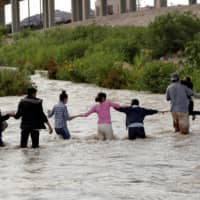 Migrants from Central America form a human chain to cross the Rio Bravo river to enter illegally into the United States to turn themselves in to request for asylum in El Paso, Texas, Tuesday.   REUTERS