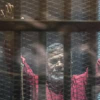 Egypt's ousted Islamist president ,Mohamed Morsi, wearing a red uniform, gestures from behind the bars during his trial in Cairo at the police academy in 2016. Morsi died Monday in a Cairo hospital after fainting in a court session, a judicial and security source said. | AFP-JIJI