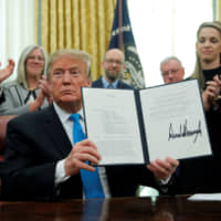U.S. President Donald Trump displays the Space Policy Directive 4 after signing it to establish a space force as the sixth branch of the armed forces in the Oval Office of the White House on Feb. 19. | REUTERS