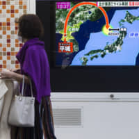 A pedestrian walks past a TV news bulletin showing a map of Japan and the Korean Peninsula during a missile launch by North Korea, in Tokyo in November 2017. | BLOOMBERG