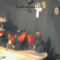 A U.S. military image released by the Pentagon in Washington on Monday that it says was taken from a U.S. Navy MH-60R helicopter in the Gulf of Oman in waters between Gulf Arab states and Iran on June 13, shows personnel that the Pentagon says are members of the Islamic Revolutionary Guard Corps Navy removing an unexploded limpet mine from the M/T Kokuka Courageous, a Japanese owned commercial tanker. | U.S. NAVY / HANDOUT / VIA REUTERS