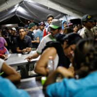 Venezuelan migrants wait in line to get vaccinated at the Ecuadorian Peruvian border service center, before continuing their journey, in the outskirts of Tumbes, Peru, Friday.   REUTERS