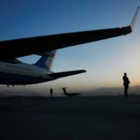 Security stands watch on the tarmac as a helicopter carries U.S. Secretary of State Mike Pompeo back to his plane after meetings in Kabul Tuesday. | REUTERS