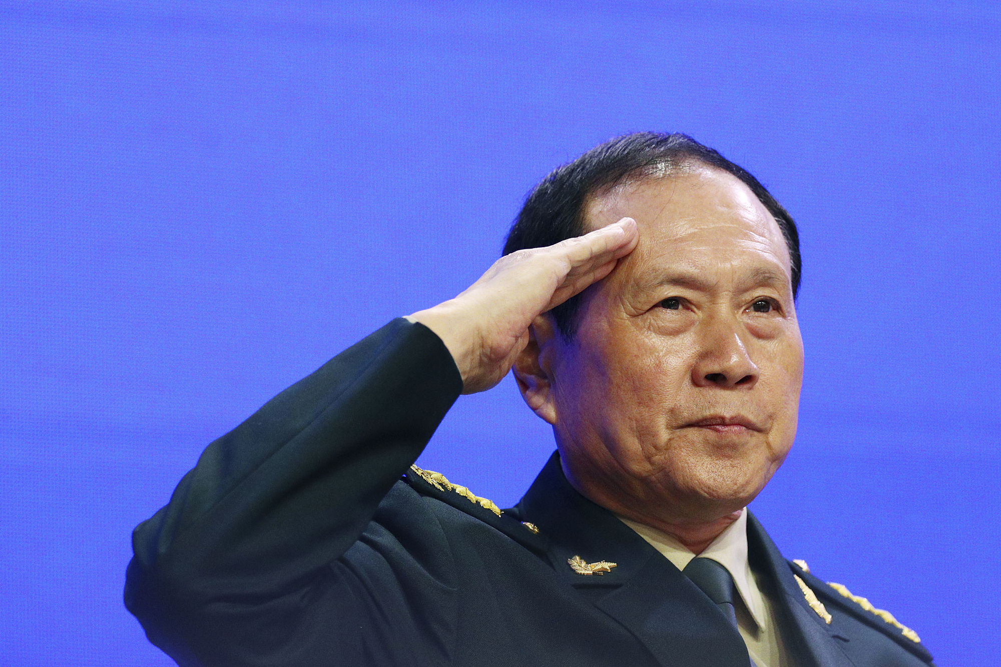 Chinese Defense Minister Gen. Wei Fenghe salutes attendees ahead of the fourth plenary session of the 18th International Institute for Strategic Studies Shangri-La Dialogue, in Singapore on Sunday.   AP